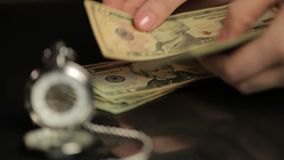 Person counting dollar bills, summing up investment results, watch showing time. Stock footage stock footage