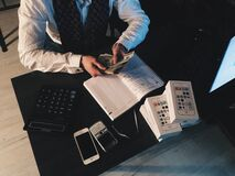 Person Counting Money With Smartphones in Front on Desk Stock Image