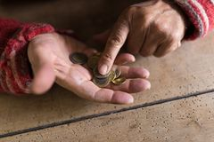 Person counting small change in palm of hand. Hands of person in old sweater counting small change in palm of old hand Royalty Free Stock Photo