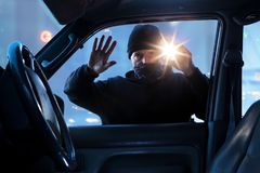 Person,criminal breaking into car at dawn, night stock photo