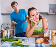 Person criticizing young spouse. Unpleased men criticizing young spouse in domestic kitchen Stock Photo