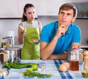 Person criticizing young spouse. Unpleased women criticizing young spouse in domestic kitchen Royalty Free Stock Photo