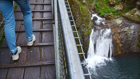 Person crossing a high bridge over a waterfall Stock Image