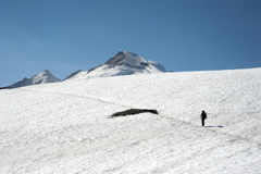 Person crossing a snowfield in the mountains Stock Image