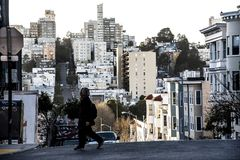 Person crossing street on steep hill in San Francisco with buildings stacked on top of each other in background. Person crossing street on steep hill in San stock photos