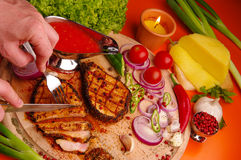Person cuts grilled meat on cutting board Royalty Free Stock Photo