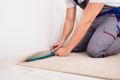 Person Cutting Carpet With Cutter Stock Image