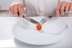 Person Cutting Cherry Tomato On platta arkivfoton