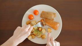 Person Cutting con la bifurcación y el cuchillo los pescados con las patatas y los tomates almacen de video