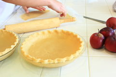 Person cutting dough for an Apple Pie. Preparing dough for and Apple Pie Stock Images