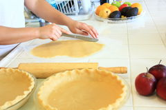 Person cutting dough for an Apple Pie. Preparing dough for and Apple Pie Royalty Free Stock Photos