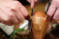 Person cutting ear of roasted pig Stock Photography
