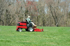 Person cutting the lawn on a riding mower Stock Images