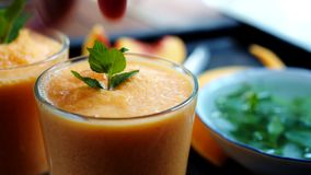 Person decorates orange smoothie