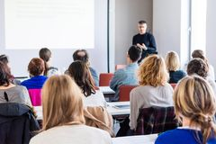 Person delivering a speach. Audience at a conference presentation Royalty Free Stock Image