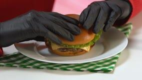 Person in den schwarzen Handschuhen, die den Schnellimbissburger reich in den Kalorien, essend nehmen zu viel stock video
