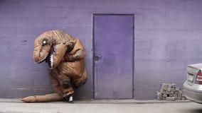 Person in der Dino-Maskottchenkostümstellung lehnt sich nahe bei Tür auf purpurroter Wand stock video