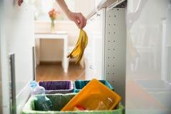 Person in der Hausküche, die Abfall trennt Stockbilder