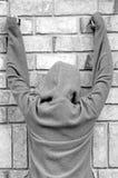 Person in der Jacke gegen Wand Stockfotografie