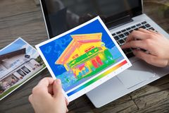 Person Detecting Heat Loss Of una casa usando el ordenador portátil fotos de archivo