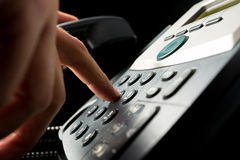 Person dialing out on a landline telephone. Punching in the numbers on the keypad with a finger, closeup side angle view on a dark background Royalty Free Stock Images