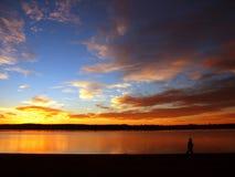 Person, die auf einen Strand am Sonnenaufgang geht Stockbild