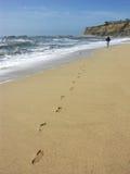 Person, die auf Strand geht Lizenzfreie Stockfotos