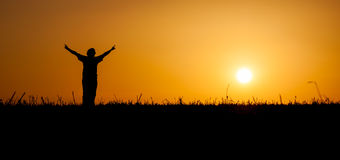 Person, die das Leben am Sonnenuntergang feiert Stockbilder