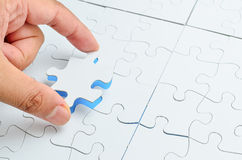 Person, die das letzte Puzzlespielstück passt Geschäftskonzept für den Abschluss des abschließenden Puzzlespielstückes Stockbild