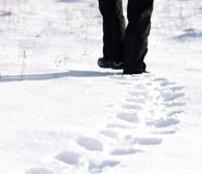 Person, die in den Schnee geht und Abdrücke lässt Stockbild