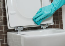 Person, die den Toilettensitz in den Gummihandschuhen säubert Lizenzfreie Stockfotografie