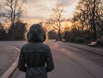 Person, die den warmen Mantel steht im Park bei Sonnenuntergang trägt Lizenzfreie Stockbilder