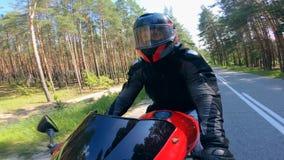 Person, die ein schnelles Motorrad auf eine Straße nahe Bäumen reitet stock video