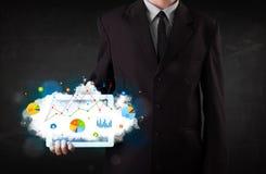 Person, die eine Berührungsfläche mit Wolkentechnologie und -diagrammen hält Stockbild