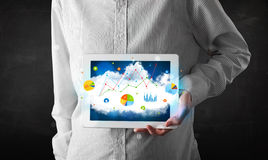 Person, die eine Berührungsfläche mit Wolkentechnologie und -diagrammen hält Lizenzfreie Stockfotos