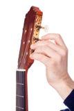 Person, die eine Gitarre von seinem Spindelkasten abstimmt Stockfotos