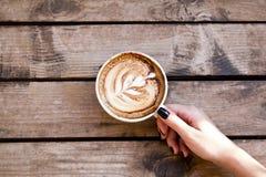 Person, die eine Kaffeetasse auf einem hölzernen Schreibtisch overhe hält lizenzfreies stockfoto