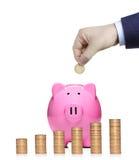 Person, die eine Münze in eine rosafarbene piggy Querneigung einsteckt Lizenzfreie Stockbilder