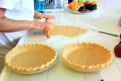 Person, die eine Pastete ohne Füllung für einen Apfelkuchen knetet stockbilder