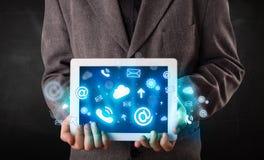 Person, die eine Tablette mit blauen Technologieikonen und -symbolen hält Stockfotos