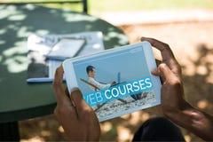 Person, die eine Tablette mit E-Learning-Informationen auf dem Schirm hält stockbilder
