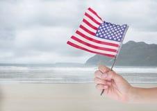 Person, die eine USA-Flagge im Strand hält Stockfoto