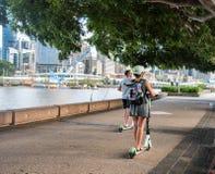 Person, die einen elektrischen Roller auf einen Fußweg reitet stockbilder