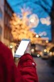 Person, die einen Smartphone auf Hintergrundglühen bokeh Weihnachten I hält stockfotografie