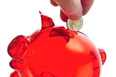 Person, die Euromünze in Sparschwein setzt Stockbilder