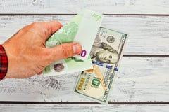 Person, die 50 Euros zu 100 Dollar ändert Lizenzfreies Stockfoto