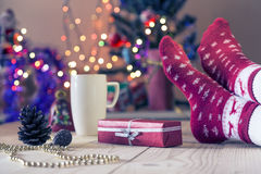 Person, die Feiertag Eve mit Geschenk und heißem Getränk genießt Stockfoto