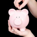 Person, die Geld in piggy banl einsetzt Lizenzfreies Stockbild