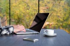 Person, die am hölzernen Schreibtisch am Computerkaffeetelefon arbeitet Stockfotos