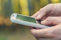 Person, die ihr Telefon im Wald am Sonnenuntergangabschluß aufbraucht Stockfoto